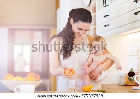 Cute little baby in the arms of her mother in their kitchen. - stock photo