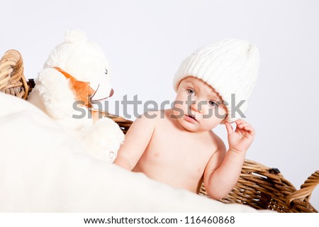 cute little baby infant in basket with white teddy bear - stock photo