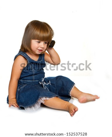 Cute little baby is talking on cell phone, isolated over white  - stock photo