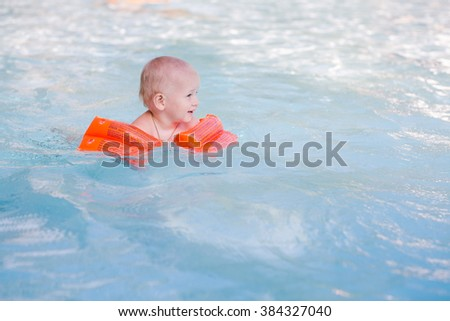 Cute little baby learning how to swim in swimming pool