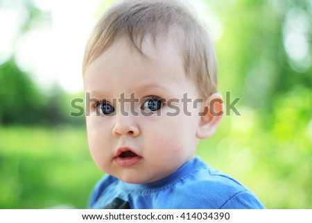 Cute little baby on summer green nature background. Pretty children infancy and people age concept. Beautiful happy girl boy child face  adorable portrait. Son daughter childhood. Wise expression kid. - stock photo