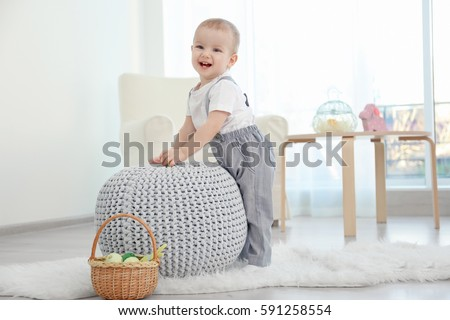 Cute little baby playing with ottoman at home