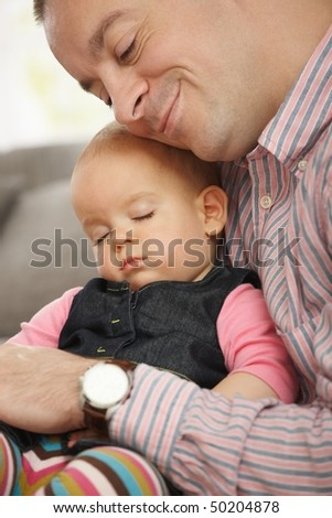 Cute little baby sleeping held in father's arm at home.