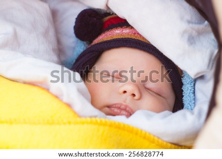 cute little baby sleeping in carriage outdoors. beautiful boy with blue eyes. child and parenthood concept. children and parents in park. adorable child, infant, kid. family lifestyle.  - stock photo