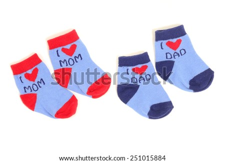 Cute little baby socks isolated on white. Small blue socks saying I love mom and dad with hearts. - stock photo