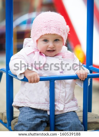 cute little baby swinging at the park - stock photo