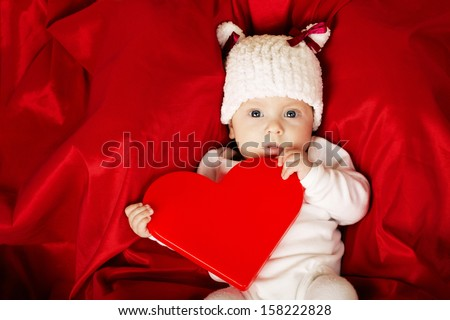 cute little baby with heart in hands - stock photo
