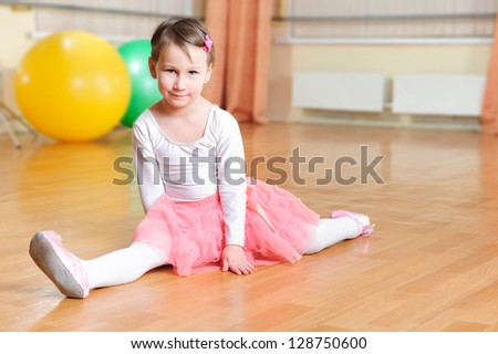 Cute little balerina stretching on floor in gymnasium