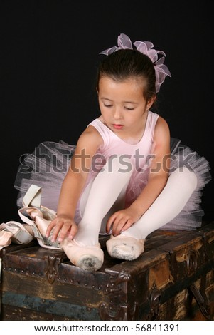 Cute little ballet girl trying on pointe shoes - stock photo