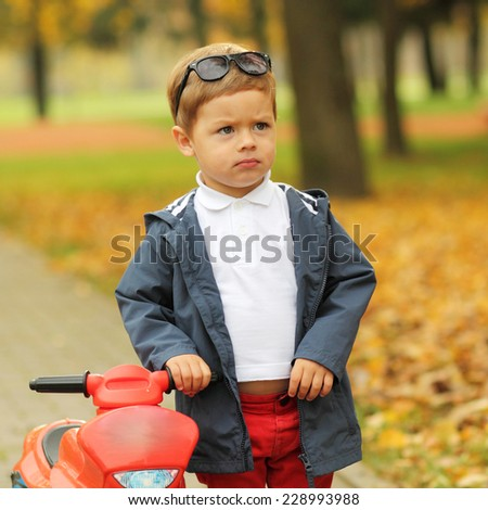 cute little biker on road with motorcycle. Young boy on toy motorcycle  - stock photo