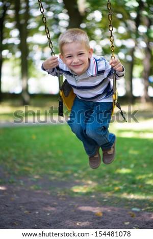 Cute little blond boy swinging on swings - stock photo