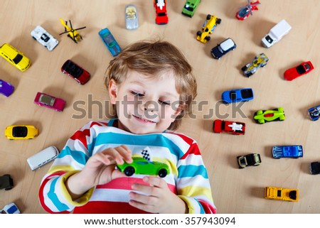 Cute little blond child playing with lots of toy cars indoor. Kid boy wearing colorful shirt. Happy preschool child having fun at home or nursery. - stock photo
