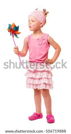 Cute little blond girl blowing windmill isolated on white background.