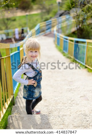 Cute little blond girl climbing a steep flight of outdoor concrete stairs up a rural hillside pausing for a rest and smiling at the camera