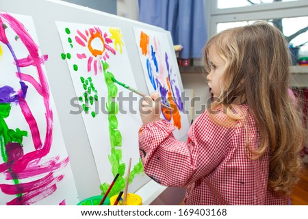 Cute little blond girl holding the brush and painting on the paper - stock photo