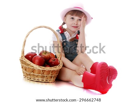 Cute little blond girl in a pink hat , denim overalls and red rubber boots sat on the ground very tired when picking apples, basket of apples costs about it on the floor - isolated on white background - stock photo