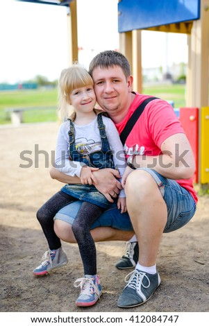 Cute little blond girl in blue jean dress sitting on knee of father with playground behind them