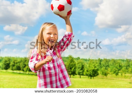 Cute little blond girl in pink shirt throwing soccer ball laughing - stock photo