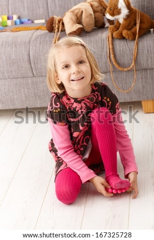 Cute little blond girl playing at home on floor, smiling. - stock photo