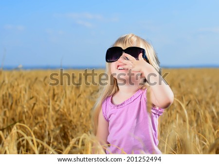 Cute little blond girl playing in a wheat field wearing a pair of large fashionable sunglasses looking up into the sun and laughing - stock photo