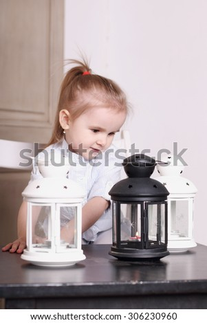 Cute little blond girl playing with three luminaires with candle. Focus on right lamp. Shallow dof - stock photo