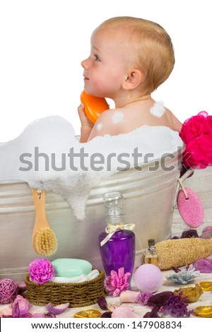 Cute little blond girl sitting in a rustic metal bathtub having a relaxing bubble bath full of soapy bubbles surrounded by luxury bathing accessories washing herself - stock photo