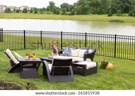 Cute little blond girl standing amongst comfortable modern design garden furniture with armchairs and tables arranged on a neat green lawn overlooking a tranquil pond and wrought iron railing - stock photo