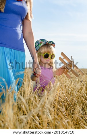 Cute little blond girl wearing trendy sunglasses walking in a field of wheat holding the hand of her mother as they enjoy the fresh air of the countryside - stock photo