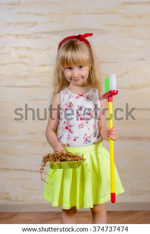 Cute little blond girl with pigtails cleaning house with a toy broom and pan proudly showing off all the wood shavings she has swept up