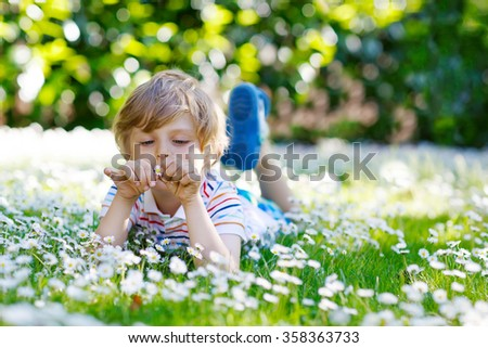Cute little blond kid boy with blue eyes laying on the grass with daisies flowers in the park. On warm summer day during school holidays. Child dreaming and smiling.