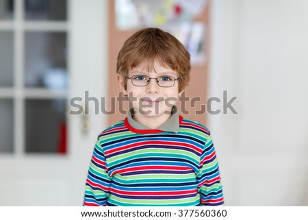 Cute little blond kid boy with eye glasses. Happy child looking at the camera - stock photo