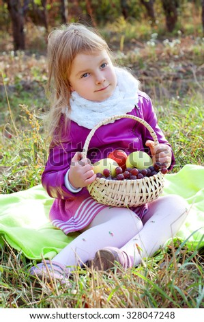 Cute little blond kid holding a basket of fruit autumn scenery
