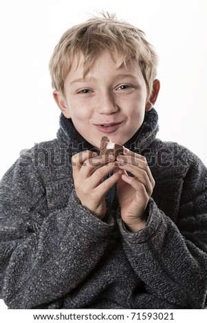 cute little blonde boy eating chocolate messily