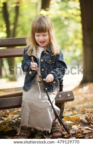 Cute little blonde girl enjoying outdoors in the city park. She siting on the park bench and playing with autumn leafs. Sunny autumn day.