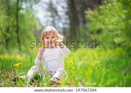 Cute little blonde girl in green grass