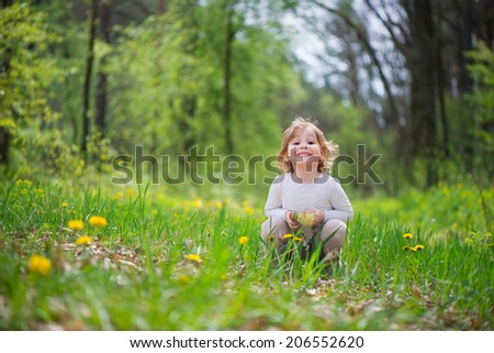 Cute little blonde girl in green grass - stock photo