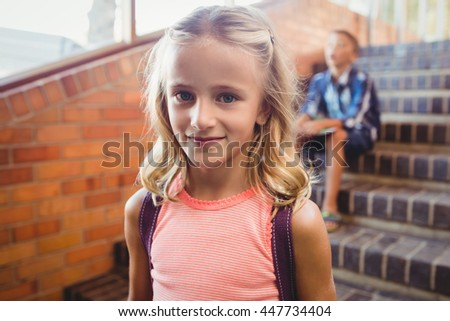Cute little blonde girl looking at the camera at school - stock photo