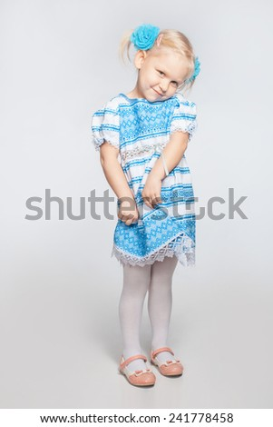 Cute little blonde girl on a white background shy - stock photo