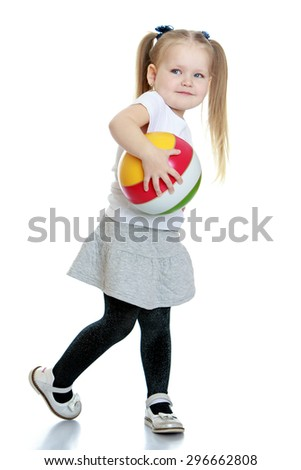 Cute little blonde girl with her hair plaited in long tails in a white t-shirt with short sleeves and a grey short skirt keeps hand striped rubber ball, pictures in motion- isolated on white - stock photo