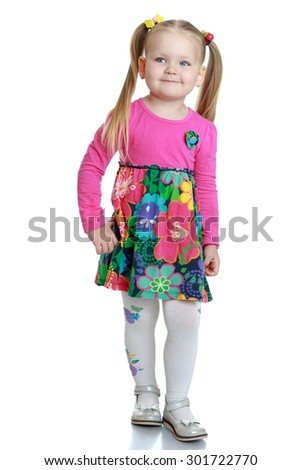 Cute little blonde girl with long tails on the head , which adheres to multi-colored gum. The girl dressed in a colorful dress. The girl is shot in the Studio with their parents-Isolated on white - stock photo