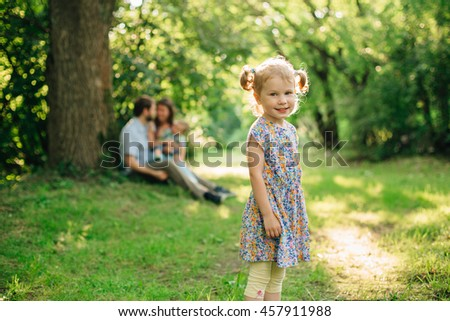Cute little blonde little girl with two pigtails  in dress standing in the park in front of her family