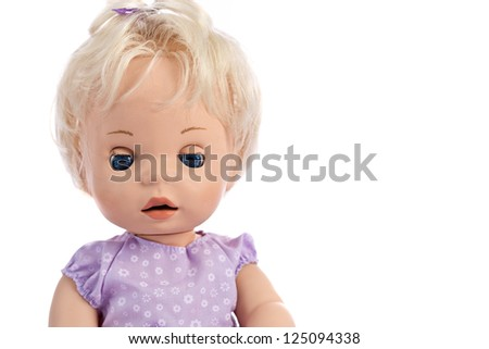 Cute little blue-eyed doll in purple dress on white background - stock photo