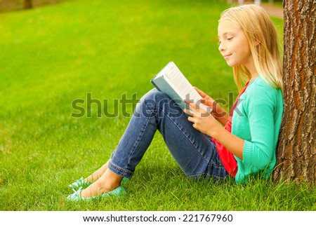Cute little bookworm. Cute little blond hair girl reading book while sitting on green grass and leaning at the tree  - stock photo
