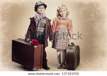 Cute little boy and girl are standing with their old suitcases. Retro style.