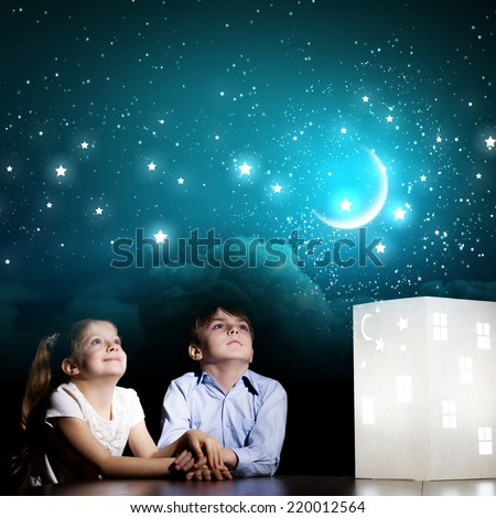 Cute little boy and girl looking at model of house - stock photo