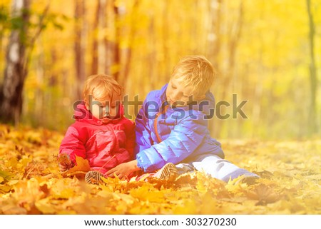cute little boy and girl playing in autumn fall leaves