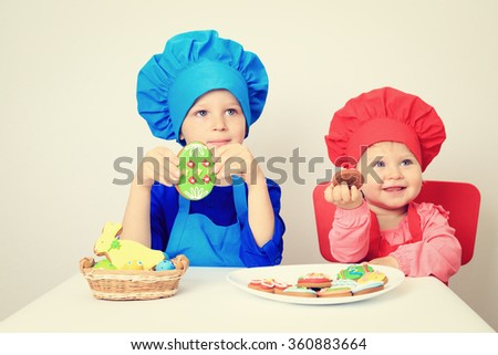 cute little boy and girl playing with easter cookies