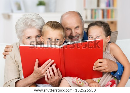 Cute little boy and girl with merry smiling eyes reading with their grandparents peering over the top of the book at the camera - stock photo