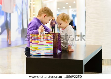 Cute little boy and girl with shopping bags in mall - stock photo