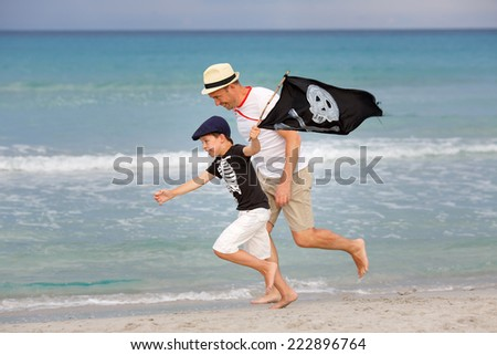 Cute little boy and his father having fun on tropical beach - stock photo